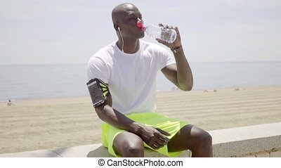 Thirsty young African man drinking bottled water as he takes...