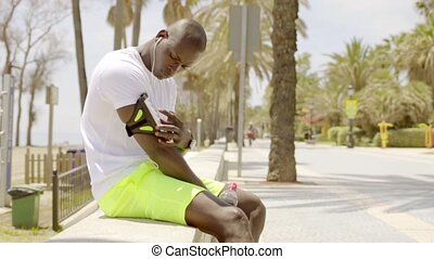 Man with device attached to arm while seated near street and...