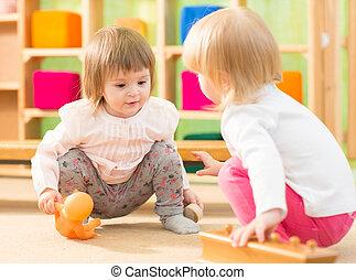 Two kids playing in kindergarten room