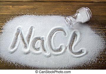 Sodium Chloride - Salt - NaCl written on a heap of salt -...