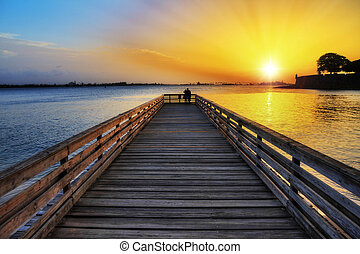 Romantic jetty San Juan - Sunset silhouette of a couple in...