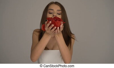 Woman blowing red rose petals - Brunette beautiful woman...