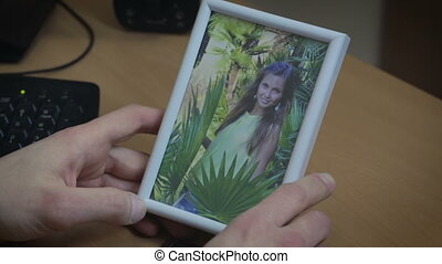 Man gently holds picture of his girlfriend - Man gently...