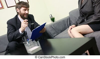 man holding sexy woman interview. He is looking at her legs.