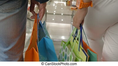 People with shopping bags going down on escalator - Man and...