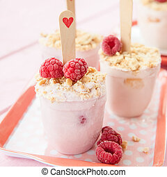 Homemade frozen popsicles with raspberries and cookie crumbs