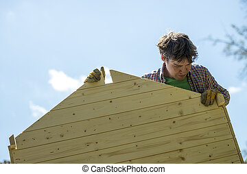 Low angle view of a young man assembling a wooden playhouse...