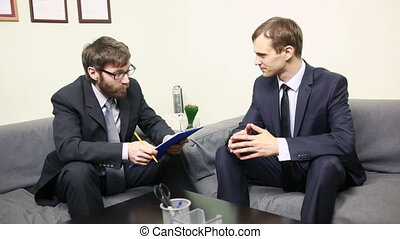 Manager interviewing a male applicant in his office. Two men...