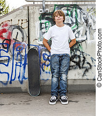 boy relaxes with his skate board at the skate park - young...