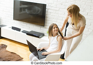 Girl on the laptop - Mother combing a daughter while on the...