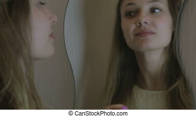 Beautiful girl straightens her hair in mirror - Beautiful...