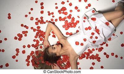Brunette woman catching rose petals - Beautiful young...