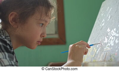 Girl draws paints on canvas - 8-year-old girl in plaid shirt...