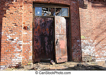 abandoned building from red brick and big metal door