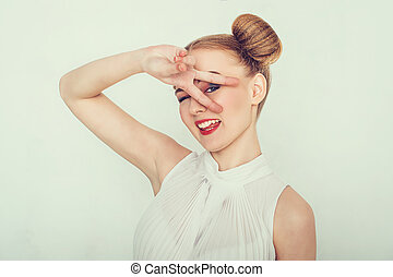 Beautiful girl with funny hairstyle. makes peace sign hands,...
