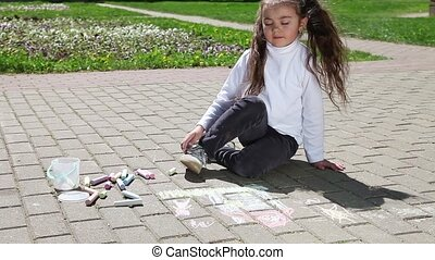 Little girl drawing on pavement wit - A little girl drawing...