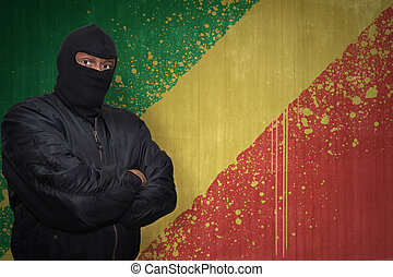 dangerous man in a mask standing near a wall with painted...