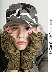 Male teen sulking while holding face in gloves - Close up of...
