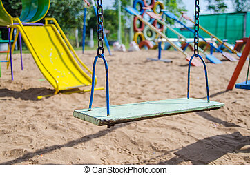 Empty swing set in playground, blank swing seat.