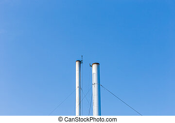 Two smokestacks on blue sky background in Thailand - Two...