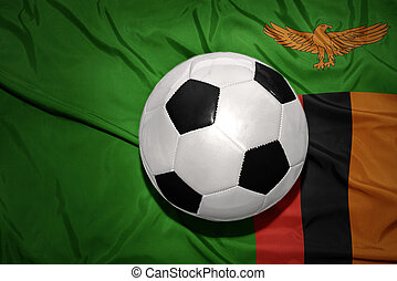 black and white football ball on the national flag of zambia...