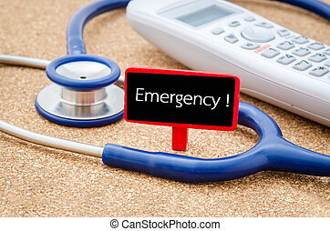 EMERGENCY HOTLINE words - Phone and stethoscope on the table...
