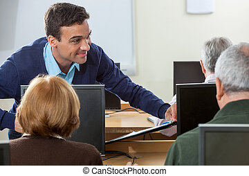 Happy Teacher Looking At Senior Students In Computer Class