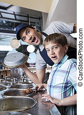 Surprised Boy With Chocolate Ice Cream Standing By Worker -...