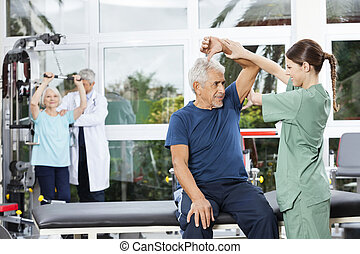 Nurse Assisting Senior Woman In Arm Exercise In Rehab Center...