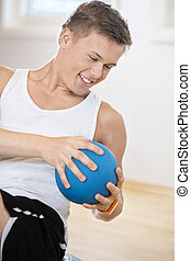 Man Exercising With Medicine Ball In Gym - Happy young man...