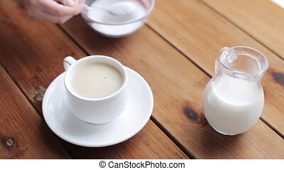 hand pouring sugar by teaspoon into coffee cup