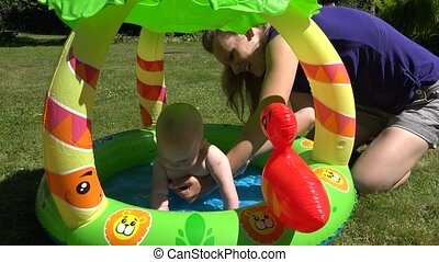 baby girl swim in rubber water pool in park Mother keep...