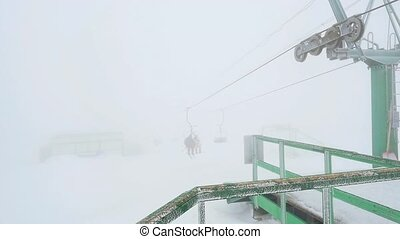 Ski, skiing - skiers on ski lift in slowmotion on snowy...