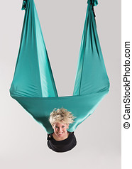 Smiling woman doing aerial yoga in mid air - Smiling mid air...