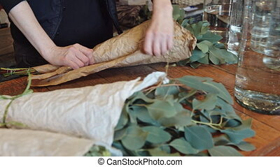 Woman florist wraps something in a sheet of parchment and...