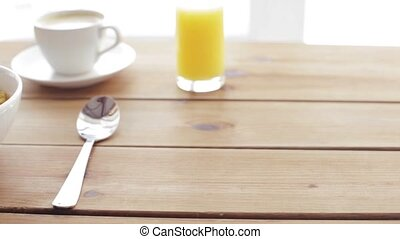 milk pouring to corn flakes on wooden table - breakfast,...