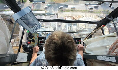 the view from the driver's cab of a construction crane,...