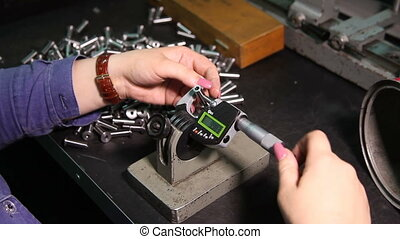 Woman measures the electronic caliper detail. - Factory man...