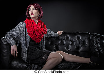 Woman Sitting on a Black Leather Couch - Fashionable female...
