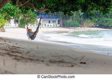 Young woman lying in the hammock on tropical beach - Young...
