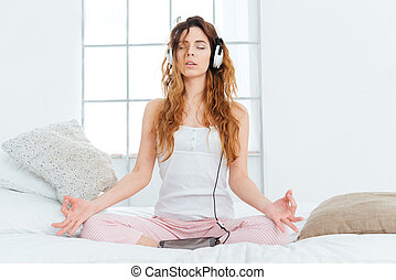 Woman meditating on the bed at home