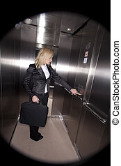business woman push button in elevator
