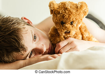 Teenage Boy Snuggling on Bed with Brown Teddy Bear - Close...