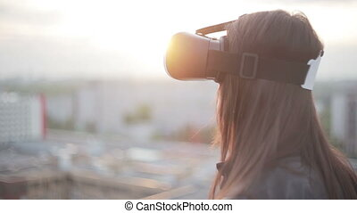 woman uses a virtual reality glasses on the roof in the rays...