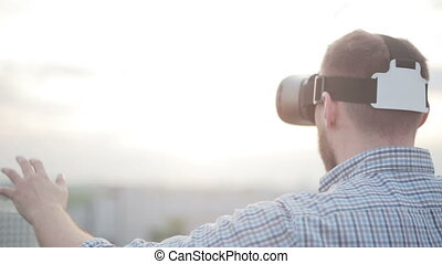 man uses a virtual reality glasses on the roof in the rays...