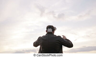 man uses a virtual reality glasses against the sky at sunset