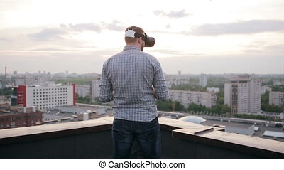 man uses a virtual reality glasses on the roof