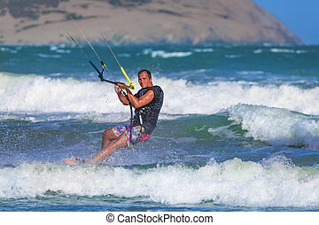 Athletic man riding on kite surf board at sea waves -...