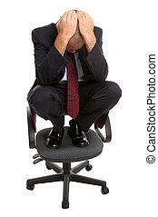Businessman crouched on a chair.