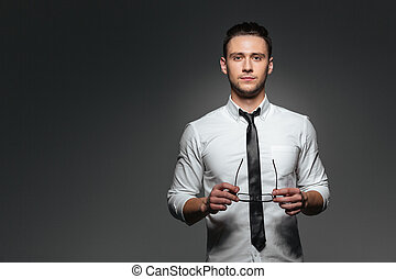 Attractive young businessman in white shirt and tie holding...